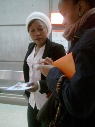 Kanicia placing magazines and sharing contact info with a woman on the metro